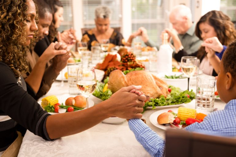 Family praying around the Thanksgiving table | Thanksgiving.com