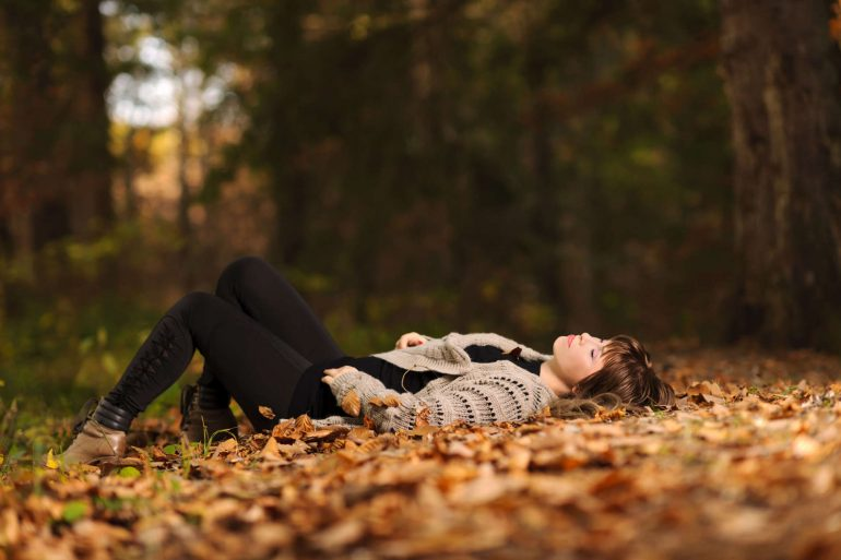 Peaceful moment as a woman sleeps in the middle of a pile of leaves | MakeItGrateful.com