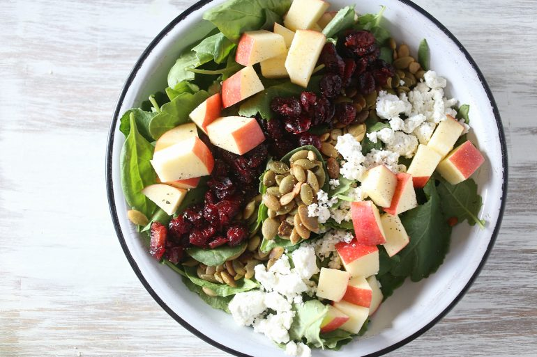 This autumn chopped kale and spinach salad has pumpkin seeds, cranberries and goat cheese -- perfect for Thanksgiving | Thanksgiving.com