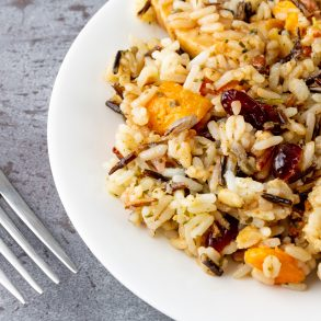 Chicken with pecans and wild rice on a plate with a fork to the side on a gray background