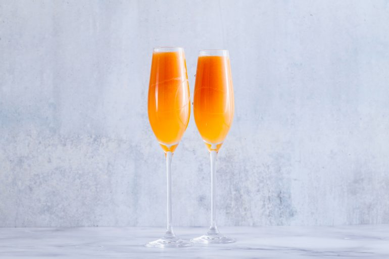 two glasses of fruit champagne on the table. refreshing festive cocktail