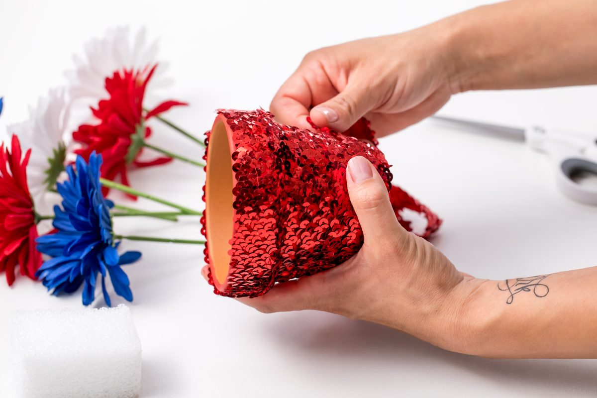 Wrap red sequin ribbon over pot