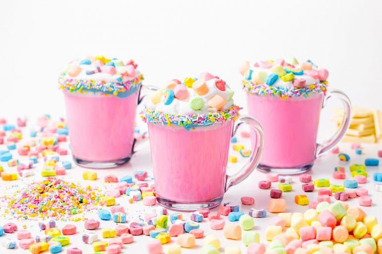 5D4B3097 - Unicorn Hot Chocolate - pink hot chocolate with whipping cream, lucky charms marshmellows on a white table