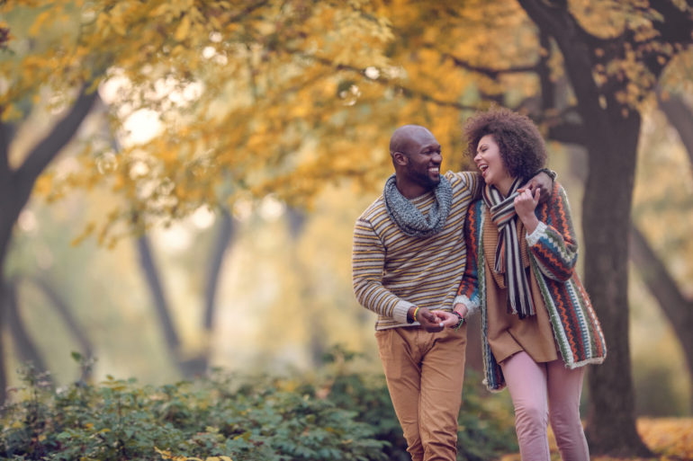 Happy African American couple walking in autumn park and laughing.