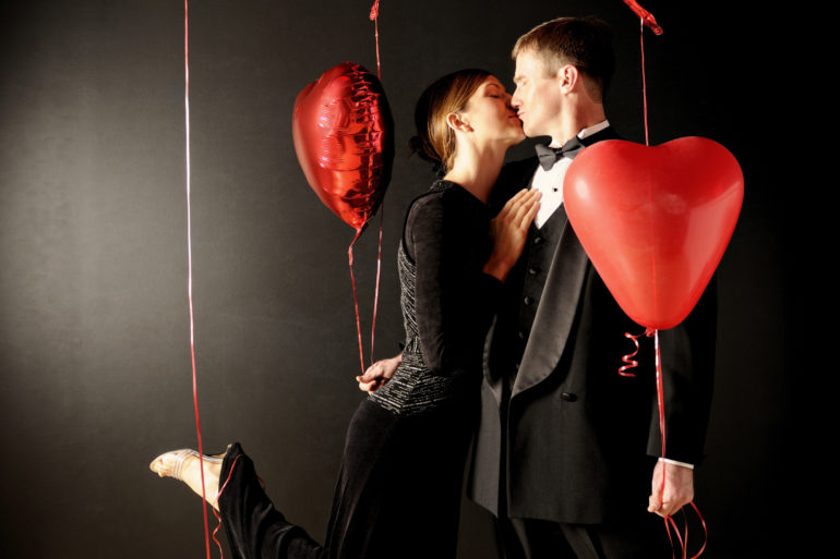 Couple kissing with heart shaped balloons
