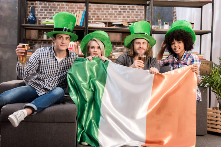 multicultural friends watching tv on saint patrick day