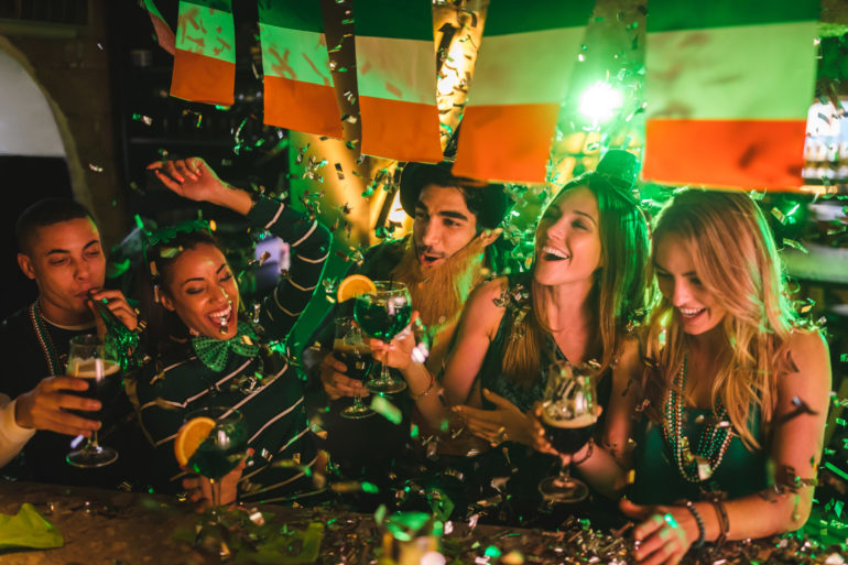 Friends partying with drinks and confetti on Saint Patrick's day