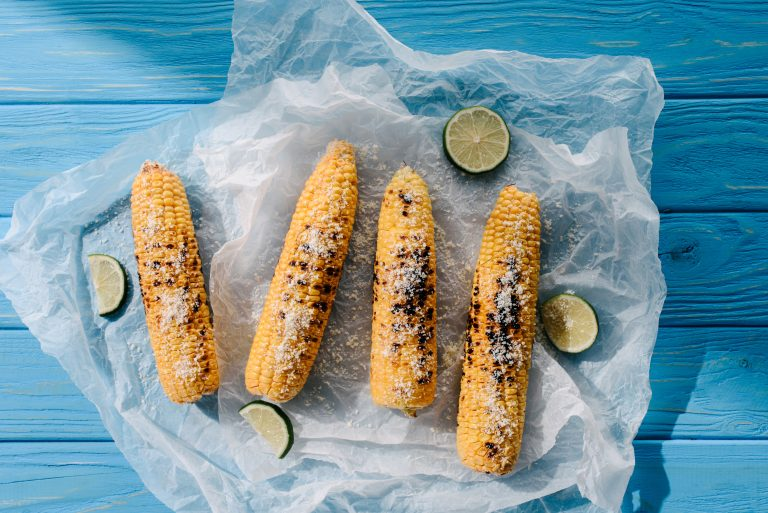 elevated view of grilled salted corn with lime slices on baking paper on wooden table