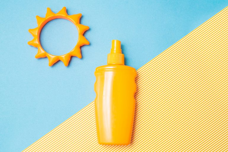 Bottle of sunscreen cream or lotion with sun toy flat lay on the blue and yellow background with copy space. Spf summer skin, uv protect top view