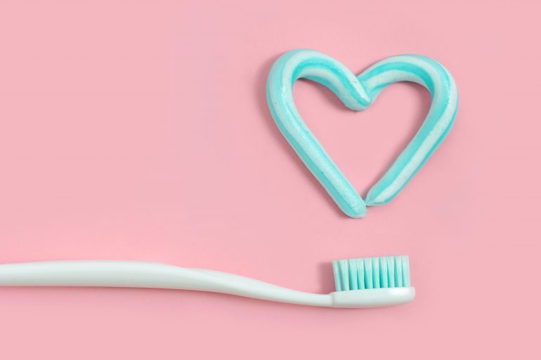 Toothbrushes and turquoise color toothpaste in shape of heart on pink background. Dental and healthcare concept.
