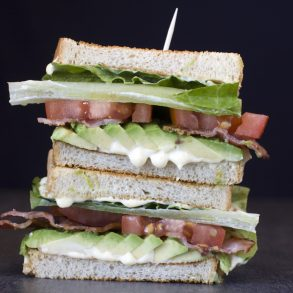 blt sandwich stacked on brown background