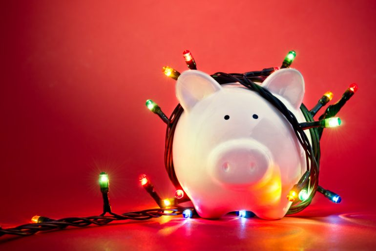 holiday stress - piggy bank wrapped in christmas lights