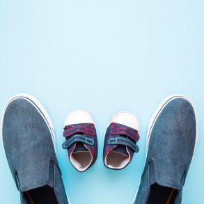 father and baby shoes flat lay paternity leave